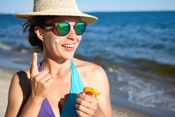 Applying sunscreen protection lotion spf. Young woman putting suntan solar cream to her cheek. Protection from burns, premature aging and skin cancer, dressed in blue swimsuit. Ocean in background