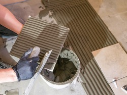 Applying thinset mortar on a tile. Apply the adhesive, closeup.