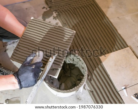 Applying thinset mortar on a tile. Apply the adhesive, closeup. Foto stock ©