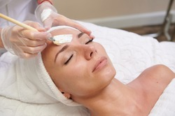 Applying white facial mask with brush in spa treatment alternative medicine