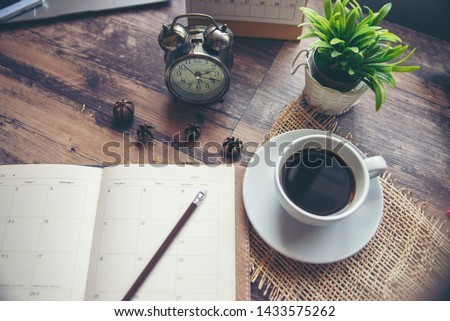 Appointment Calendar Concept.Desktop Calender, Diary, Coffee place on office desk, work online at home. Notebook for Planner plan timetable, agenda, appointment management each date, month and year.