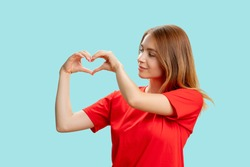 Appreciation sign. Love affection. Portrait of supportive kind woman in red t-shirt showing heart gesture isolated on blue background. Romantic message.