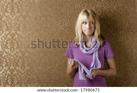 Apprehensive young girl leaning against a wall with gold wallpaper
