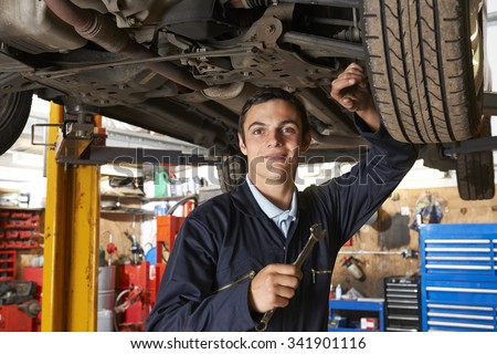 Apprentice Mechanic Working On Car #341901116