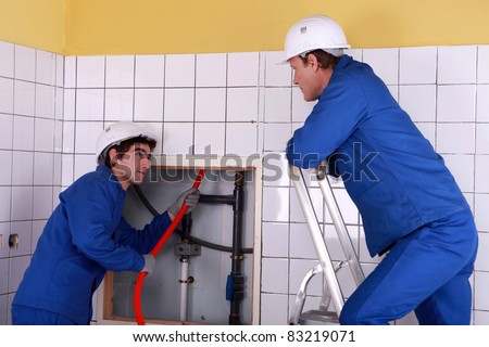 Apprentice passing red cable up behind a tiled wall