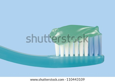 Approach to a toothbrush with toothpaste on a blue background.