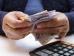 approach to hands of a senior woman counting Danish banknotes and calculator