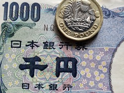 approach to japanese banknote of 1000 yen and coin of one sterling pound, background and texture
