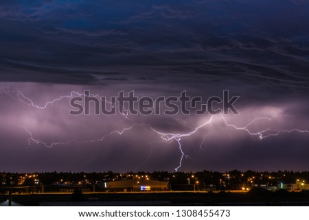 approaching storm clouds with sheets of lightning over the city lights