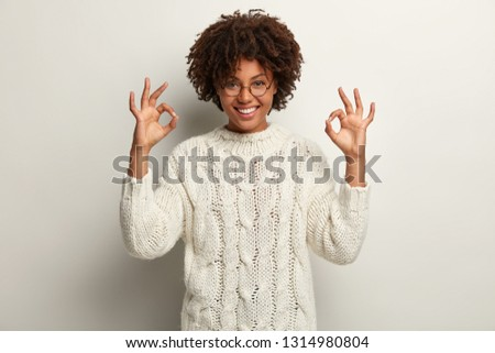 Approval and agreement concept. Picture of happy black ethnic woman makes okay gesture with both hands, says everything is super or perfect, dressed in white jumper, proceeds according to plan