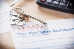 Approved mortgage loan agreement application with house shaped keyring
