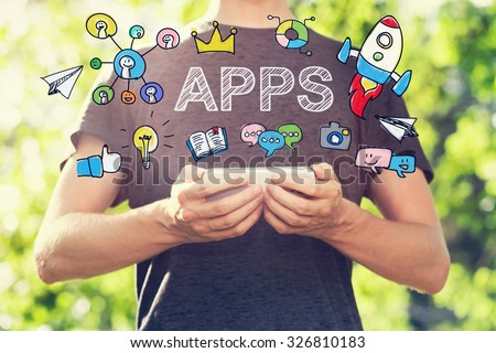 APPS concept with young man holding his smartphone outside in the park toward sunset