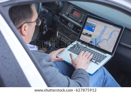 APR 24, 2017 NEY YORK, USA: Adult man sitting in car with Google maps on his laptop. #627875912