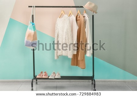Apricot clothes and accessories on rack near trendy color wall #729884983