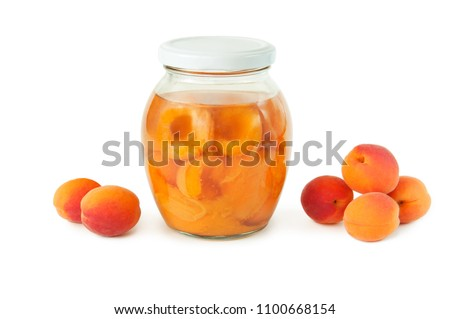 apricot compote in a glass jar and a bunch of ripe apricots on a white background. sweet and healthy dessert