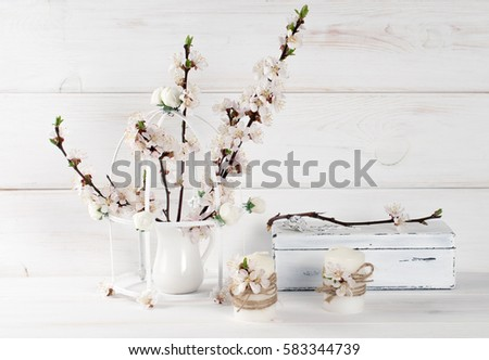 Apricot flowers in vase, candle and old vintage casket with rose in Shabby Chic style. Spring interior. #583344739