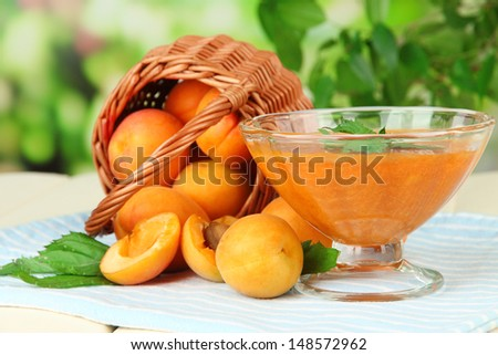 Apricot jam in glass bowl and fresh apricots, on wooden table, on bright background