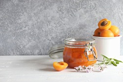 Apricot lavender marmalade in a glass jar on a rustic wooden table