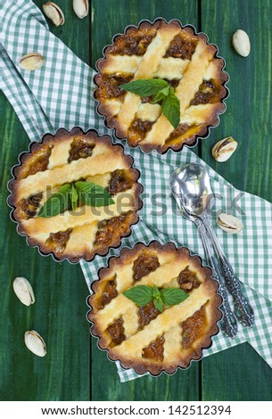 Apricot pie with pistachio on green table