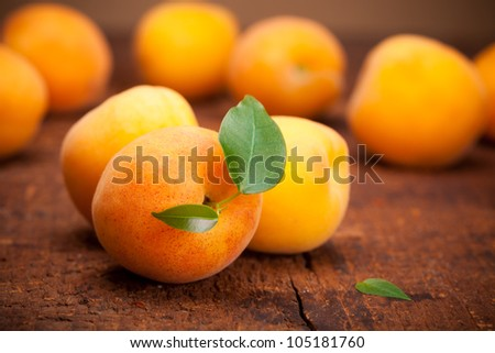 apricot with leaf on wooden background - stock photo