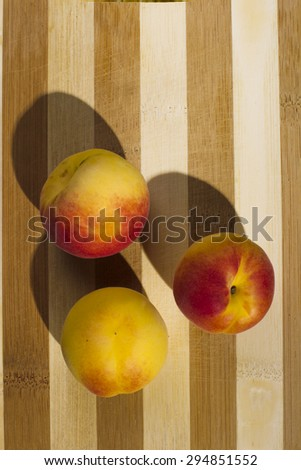 Apricots casts a shadow on the striped wooden background illuminated studio lights, the view from the top.