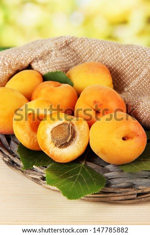 Apricots on wicker coasters on wooden table on nature background
