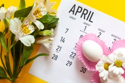 April 2020 calendar, cute pure white easter eggs and white flowers on yellow background. April 2020 monthly calendar. Top view. View from above. Monthly April calendar