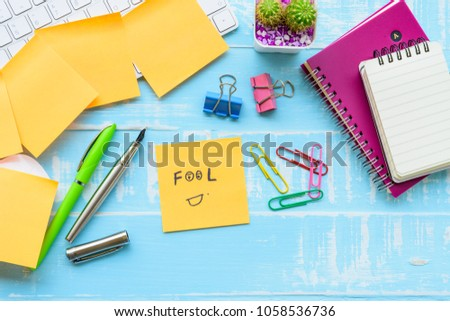 April fool's day celebration concept. office table with office accessories laptop, keyboard, mouse covered in sticky notes  on blue wooden background. #1058536736