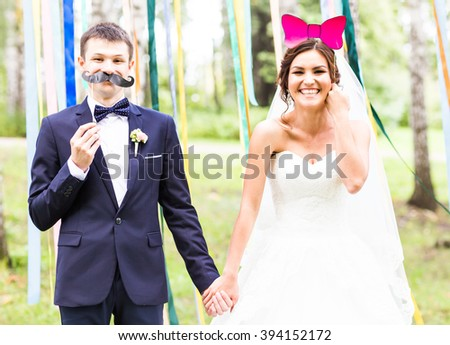 April Fools' Day. Wedding couple posing with mask. #394152172
