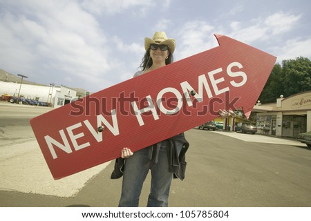 APRIL 2007 - Girl holding red sign with arrow pointing up, that reads New Homes For Sale in Santa Paula, California