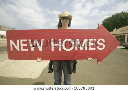 APRIL 2007 - Girl holding red sign with arrow, that reads New Homes For Sale in Santa Paula, California