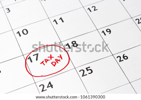 """April monthly calendar with 17th circled with words """"Tax Day"""" written in circle in red marker. #1061390300"""