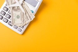 April of the year is Tax Day, Top view flat lay closeup calculator and Dollar money, on yellow background business finance budget concept with copy space for text