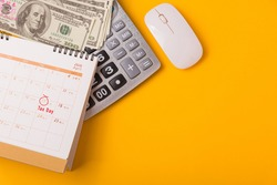 April of the year is Tax Day, Top view flat lay closeup calculator, laptop computer, calendar, and Dollar money, on yellow background business finance budget concept with copy space for text