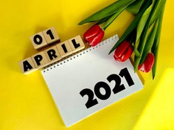 April 1 on wooden cubes.Next to it are tulips and a white notebook with the inscription 2021 on a yellow background.Calendar for April.