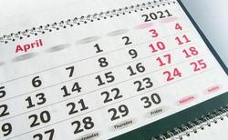April 2021 paper calendar planner with spiral, close-up.