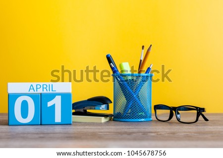 April 1st. Day 1 of april month, calendar on table with yellow background and office or school supplies. Spring time