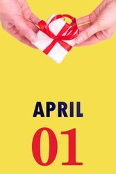 April 1st. Festive Vertical Calendar With Hands Holding White Gift Box With Red Ribbon And Calendar Date 1 April On Illuminating Yellow Background. Spring month, day of the year concept.