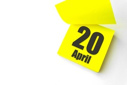 April 20th. Day 20 of month, Calendar date. Close-Up Blank Yellow paper reminder sticky note on White Background. Spring month, day of the year concept