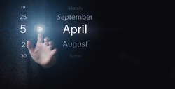 April 5th. Day 5 of month, Calendar date. Hand click luminous icon PLAY and DATE on dark blue background. Spring month, day of the year concept