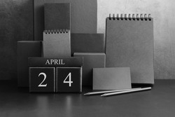 April 24th. Day 24 of month. Wood cube calendar with date month and day. Trendy classic black color. Lot of empty pages template for daily notes.