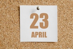 April 23. 23th day of the month, calendar date.White calendar sheet attached to brown cork board. Spring month, day of the year concept.