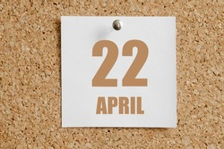 April 22. 22th day of the month, calendar date.White calendar sheet attached to brown cork board. Spring month, day of the year concept.