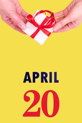 April 20th. Festive Vertical Calendar With Hands Holding White Gift Box With Red Ribbon And Calendar Date 20 April On Illuminating Yellow Background. Spring month, day of the year concept.