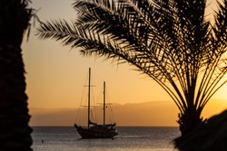 Aqaba harbor with sailing ship in the sunset on the red sea