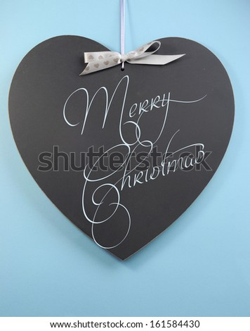 Aqua blue theme Merry Christmas message greeting written on heart shape blackboard.