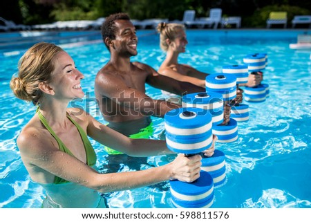 Aqua fitness at resort. Two healthy smiling young women with dumbbells and their male instructor standing at swimming pool and doing exercise on summer day outdoors