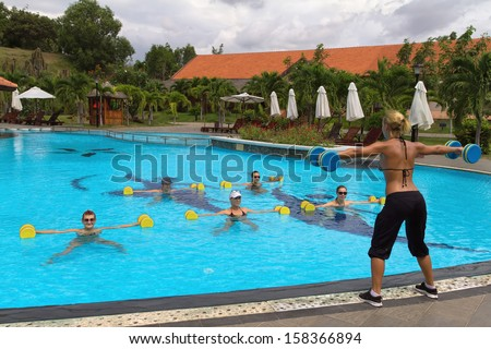 Aqua Gym: aerobics / fitness instructor in front of a group of people in the water performing exercises.