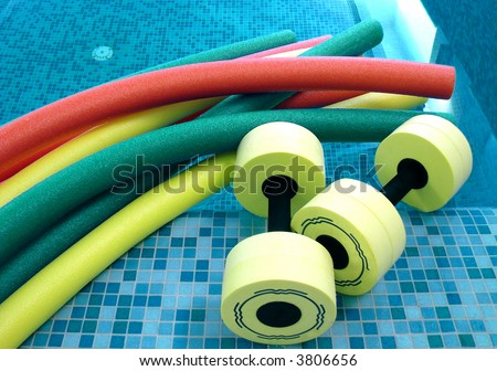 aqua noodles dumbbells for aqua aerobics lie on the coast in pool