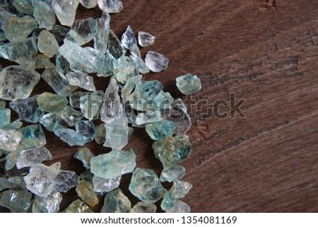 Aquamarine gemstone on wood background. Aquamarine crystal.  #1354081169